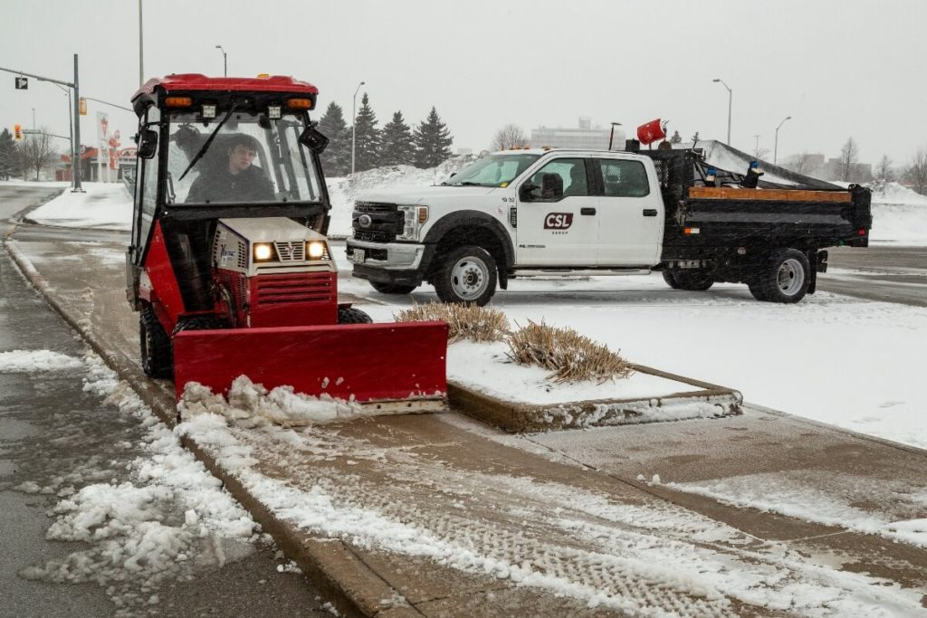 clearing snow from a sidewalk | How To Prepare Your Commercial Property For Winter